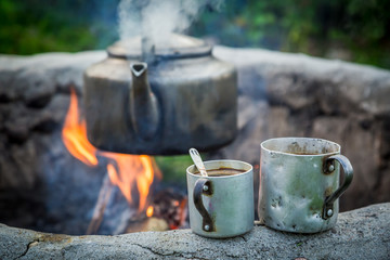Hot and aromatic coffee with kettle on bonfire