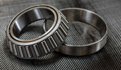 Automotive tapered roller bearing and race on carbon fiber cloth