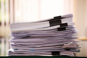 Close up paper stack on the desk related to business functions.Stack of business document files,report paper of accounting and financial with morning light,soft focus