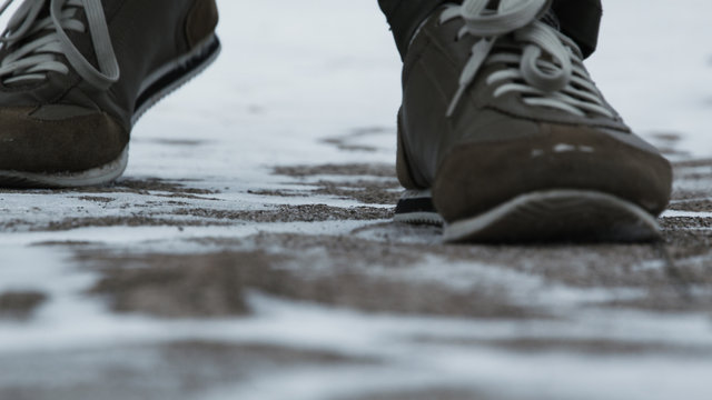 Close-up of male legs in winter shoes walking on snow. Footage, View of walking on snow with Snow shoes and Shoe spikes in winter. Men's legs in boots close up the snow-covered path