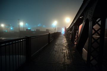 Wall Mural - Dramatic industrial vintage river bridge scenery at night with illuminating fog in Chicago.