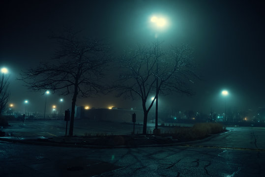 An eerie and foggy city night by a large empty urban shopping mall parking lot.