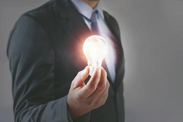 concept businessman holding lightbulb. idea inspiration and new innovation for saving energy