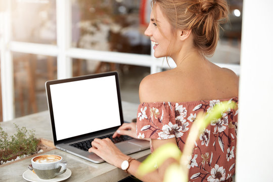 Back view of slim young female prepares project on laptop computer while sits at coffee shop and drinks tasty cappuccino. Unrecognizable woman in front of modern electronic device with blank screen