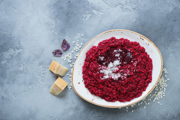 Plate of beetroot risotto on a grey stone background, horizontal shot with space, flat-lay