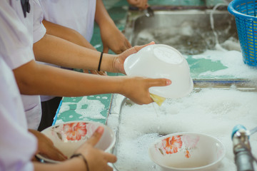 Close up to hands of primary school students are cleaning dishes.