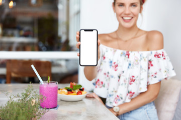 Cheerful restful woman sits at restaurant, enjoys fresh fruit and beverage, holds smart phone with blank white screen for your promotional text or advertisment. People, technology, lifestyle concept