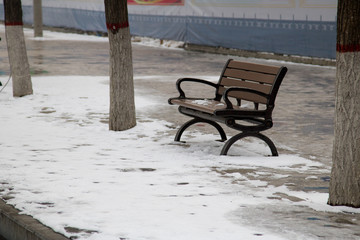Chair in park In winter with snow