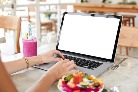 Successful female freelnacer uses laptop with blank screen during vacations in exotic country, does remote job, surrounded with fresh smoothie and fruit salad, enjoys free internet connection in cafe.