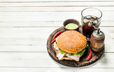 Fresh burger with cola on a wooden board.