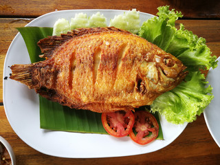 fried fish with vegetable on white dish top view, Delicious Asian fish fry served on a wooden table.