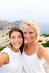 Girlfriends taking selfie photo with phone. Two beautiful young women best friends self-portrait picture on summer vacation. Multiracial asian brunette woman, blonde woman on Europe Spain travel trip.