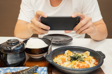Close-up Man's hands use pointing finger Mobile smart Phone take photo Food on table, technology and home concept