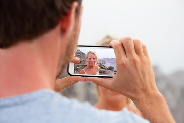 Tourist taking picture with mobile phone of his girlfriend at travel summer vacation destination. Man holding smartphone taking a photo touching screen of cellphone outdoors.