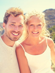 Beautiful young couple of happy Caucasian people outdoor lifestyle. Smiling blonde woman and man in their 20s. Summer portrait outside.