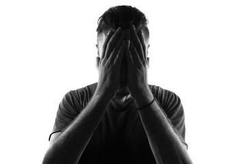 Male person silhouette crying and covering the face with the hands hiding the tears,back lit