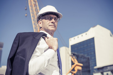 Senior elegant builder man in suit at construction site on sunny