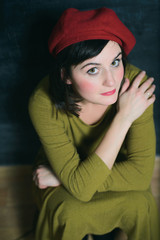 woman in red beret and green dress sitting near the black wall
