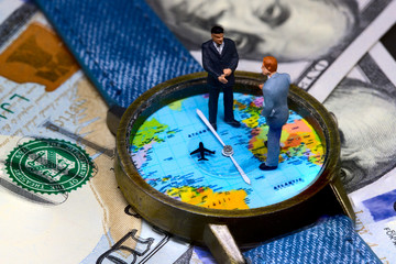 Two businessmen figurines on time and money background. Worldwide business concept.