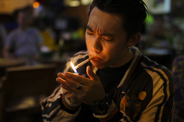 man lighting cigarette at outdoor seating outside a pub or bar