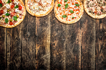 variety of pizzas. On wooden background