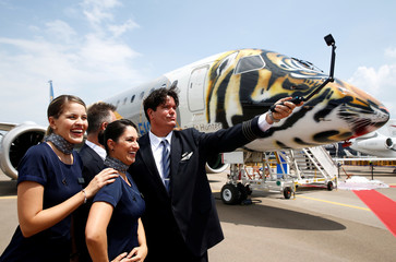 Embraer employees pose for photos next to an Embraer E-190 E2 aircraft featuring a spray painted tiger face on the nose of the aircraft displayed at the media preview of the Singapore Airshow