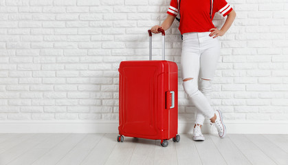 concept travel and tourism. legs of  girl with a red suitcase near white empty brick wall