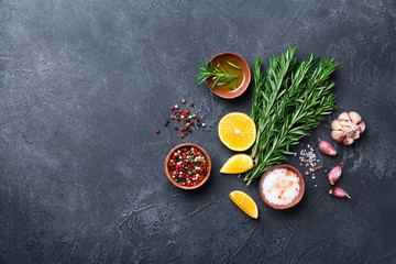 Fresh rosemary and mixed spices on black stone table top view. Ingredients for cooking. Food background.