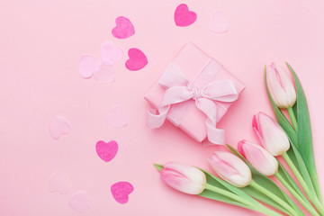 Spring flowers and present or gift box on pink pastel table top view. Greeting card for Womans or Mothers Day. Flat lay.