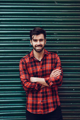 Young bearded smiling man wearing a plaid shirt with a green blind behind him.