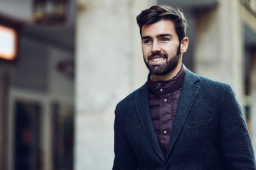 Young bearded smiling man wearing british elegant suit in the street.