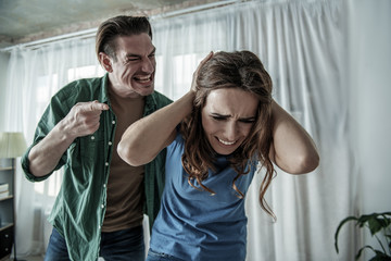 You are miserable. Aggressive man is screaming at woman with irritation. Lady is crying with horror