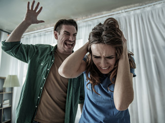 Terrified woman is covering her head while cruel man is going to hit her. Family violence concept