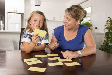 happy young mother and her sweet and beautiful little daughter playing card game at home kitchen smiling and having fun together