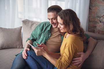 Cute loving couple using tablet while relaxing at home. They are sitting on sofa and smiling