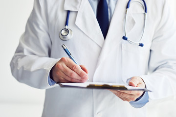Male doctor writes notes on clipboard in office
