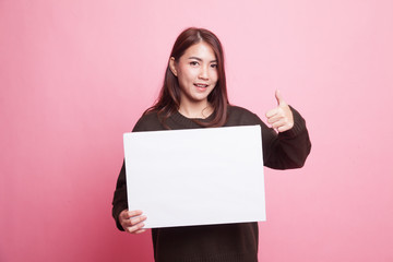 Young Asian woman show thumbs up with  white blank sign. Wall mural