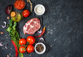 Raw marbled meat steak with ingredients for cooking on dark stone background