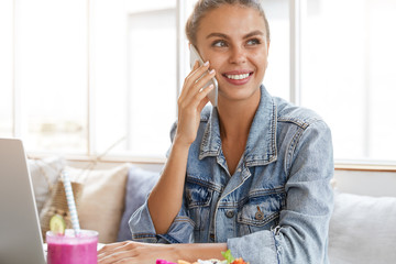 Happy beautiful female model with pleasant smile, has telephone conversation with boyfriend, sits in front of opened laptop computer, drinks tasty cocktail. Woman enjoys online communication indoor