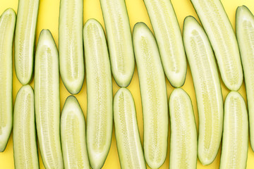 Cut lengthwise cucumbers laid out in a row on a yellow background
