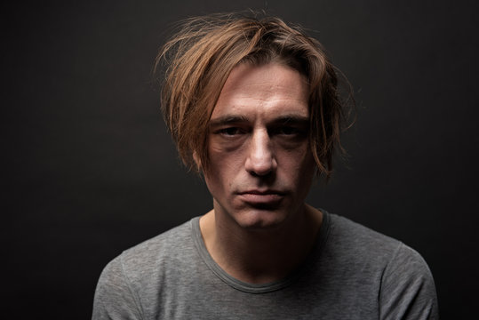 Portrait of exhausted sad guy with shaggy hair standing and looking at camera with apathy. Isolated on background