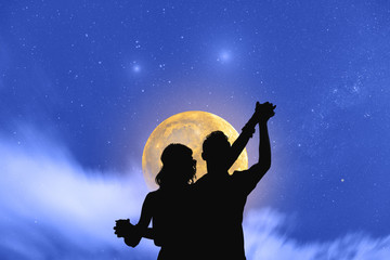 Young couple dancing under the moonlight and stars.