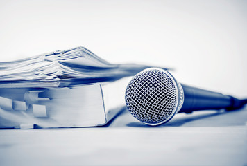 Close up a Microphone with paper document , concept of speaker or teacher preparation to speak in seminar class room