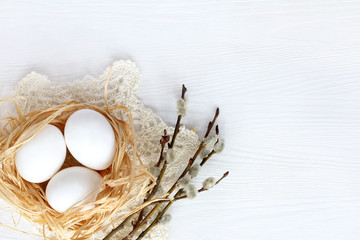 Easter holiday/ Three chicken eggs in a nest on a lacy napkin and five willow twigs
