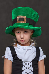 young girl in green leprechaun hat and black laced vest looking at camera