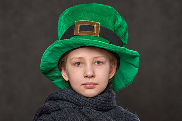 young girl in green leprechaun hat and grey knitted scarf looking at camera
