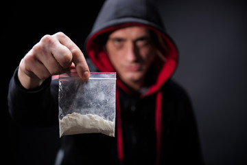Addiction concept. Sly drug dealer holding package with drugs. Focus on hand with narcotic. Isolated on background