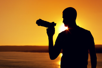 Rear view - silhouette of photographer taking pictures with zoom lens against background of sea surface on warm sunny day during sunset
