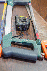 handsaws and measuring tape on wooden background
