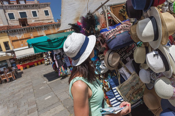 Young tourist looking at the goods in souvenir stand in Venice. Shopping on vacation